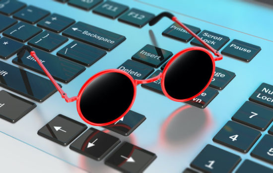 Dreaming summer vacation at work. Sunglasses red round frame with black lens, on computer keyboard, 3d illustration